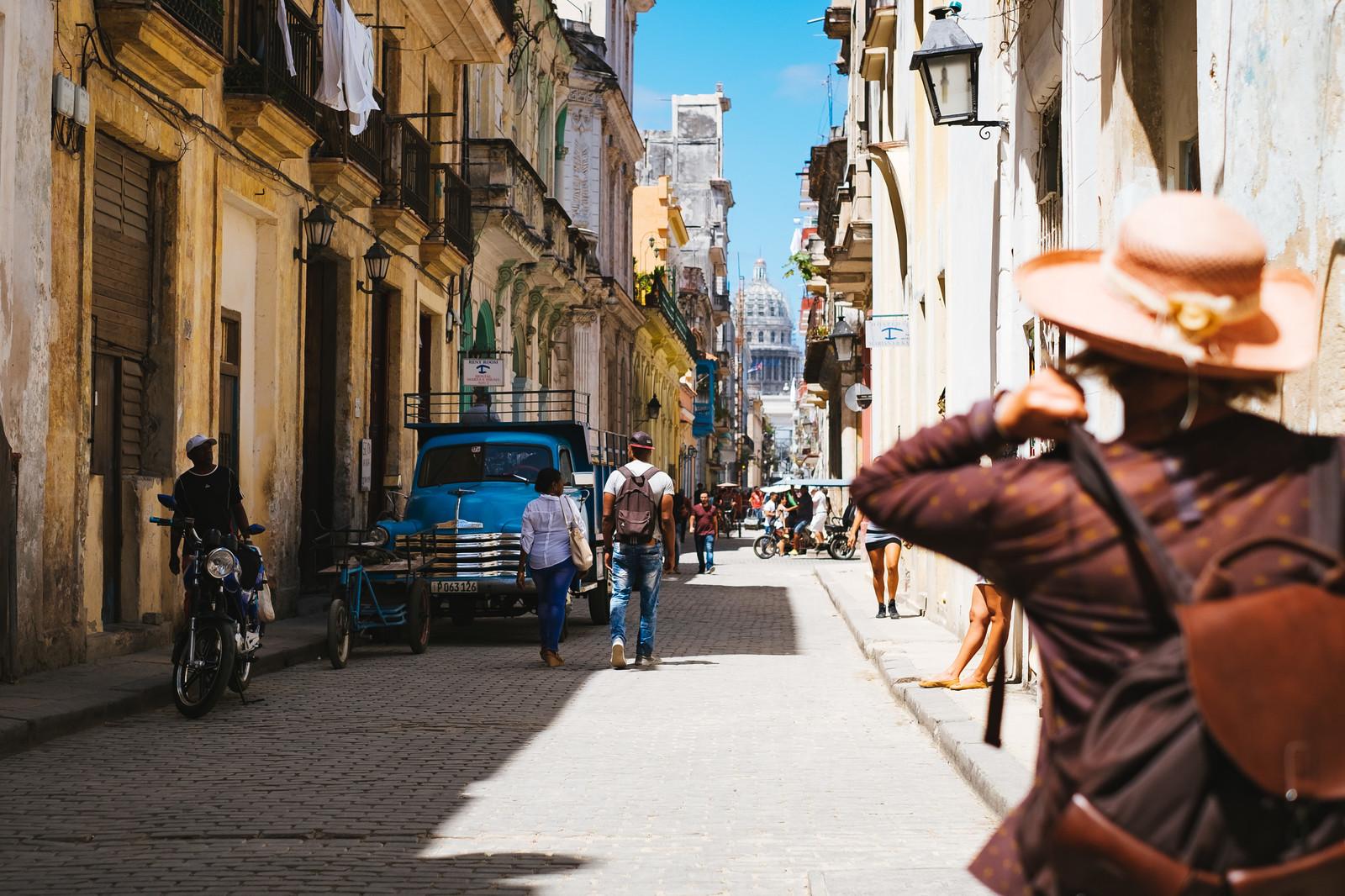 バカンスで街を詮索する旅人とキューバの街並み