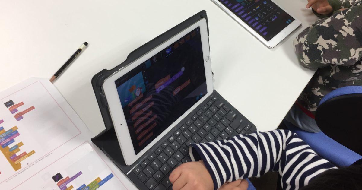 タブレット端末でプログラミングをする子どもたち