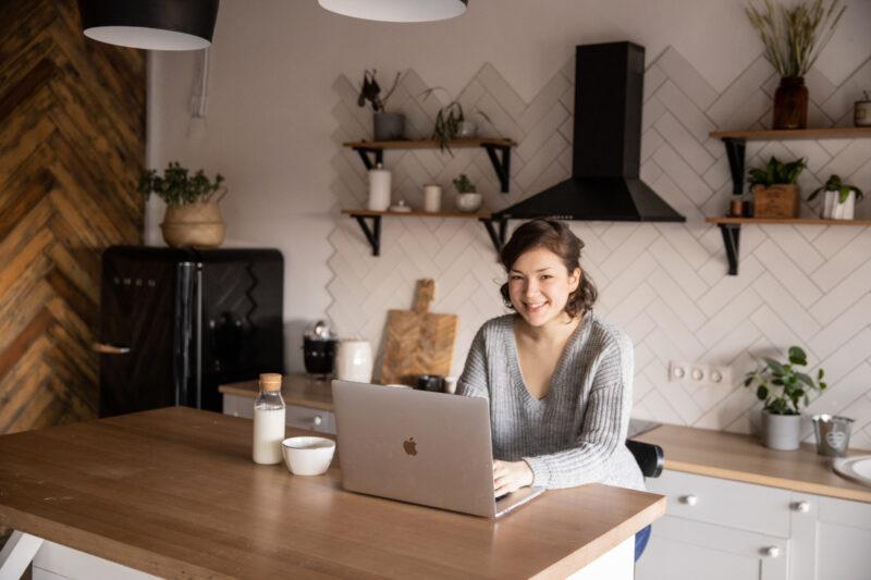 キッチンでラップトップPCを使う女性